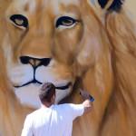Gela López añade un león a su mural de animales de sabana africana