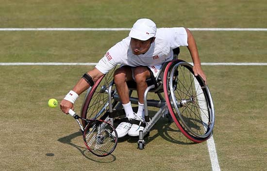 Japan's Shingo Kunieda in action with team-mate France's Stephane Houdet during the Men's Wheelchair Doubles Final during day thirteen of the Wimbledon Championships at The All England Lawn Tennis and Croquet Club, Wimbledon.