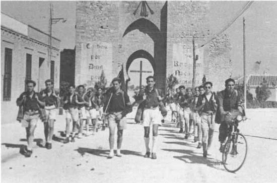 Una centuria del Frente de Juventudes con la Puerta de Toledo al fondo en el Ciudad Real de posguerra
