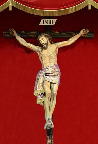 Crucificado de talla en nogal policromado, de 1,80 m sin la cruz, para la Iglesia de su título en Torrenueva. Es imagen procesional.