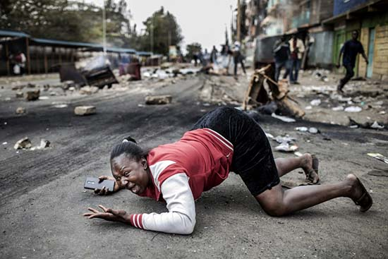 A woman reacts as she passes Kenyan police troops during a protest by supporters of the National Super Alliance (NASA) presidential candidate on August 11th, 2017 at the Mathare slum of Nairobi, a stronghold of Kenyan opposition leader.